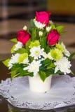 Rote Rosen und weiße Blumen Stockfoto