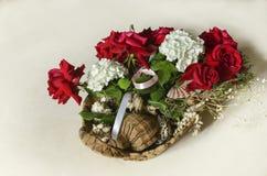 Rote Rosen, weiße Hortensien, verziert mit Niederlassungen des Eukalyptus mit Muscheln in einem Strohkorb Stockbilder