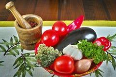 Rote runde Schüssel mit Frischgemüse, olivgrüner hölzerner Mörser, Tischdecke mit Oliven Stockfotografie