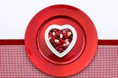 Rote Süßigkeitsherzen auf roter Platte Stockbild