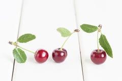 Rote saftige Kirsche auf dem weißen Holztisch Lizenzfreies Stockfoto