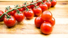 Rote saftige Tomaten auf einem Schneidebrett Stockfotografie