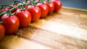 Rote saftige Tomaten auf einem Schneidebrett Lizenzfreie Stockbilder