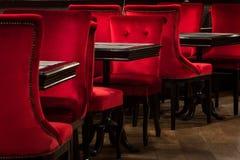Rote Samtstühle und schwarze Tabellen Stockfoto
