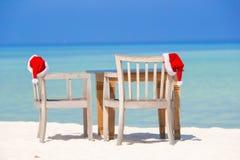 Rote Sankt-Hüte auf Strandstuhl an den tropischen Ferien Lizenzfreie Stockfotos