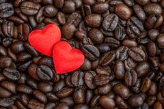 Rote Satinherzen auf Kaffeebohne-, Valentinsgruß- oder Muttertageshintergrund, Liebesfeiern Lizenzfreie Stockbilder