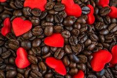 Rote Satinherzen auf Kaffeebohne-, Valentinsgruß- oder Muttertageshintergrund, Liebesfeiern Lizenzfreie Stockfotos