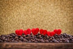 Rote Satinherzen auf Kaffeebohnen mit Buchstabe-, Valentinsgruß- oder Muttertageshintergrund, Liebesfeiern Lizenzfreies Stockbild