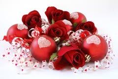 Rote Satinkugeln, mit Rosen und Farbband. Stockfotografie