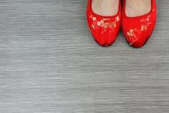 Rote schöne chinesische orientalische Schuhe auf hölzernem Hintergrund stockfotos