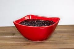 Rote Schüssel füllte mit der schwarzen Bohnensuppe, die auf dem Küchentisch essfertig ist lizenzfreie stockfotografie