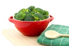 Rote Schüssel mit Brokkoli und hölzernem Löffel auf Teetuch lizenzfreies stockfoto
