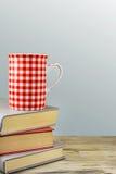 Rote Schale über Büchern auf grauem Hintergrund. Lizenzfreies Stockbild