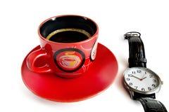 Rote Schale über Kaffee und eine Uhr auf einem weißen Hintergrund Stockfoto