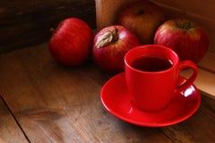 Rote Schale Apfelwein und rote Äpfel auf hölzerner alter Tabelle Retro- gefiltertes Bild Stockbild
