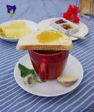 Rote Schale Kakao und Brot Stockfotos