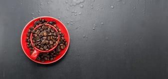 Rote Schale und Kaffeebohnen auf einem schwarzen Hintergrund, Stockbild