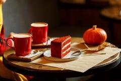 Rote Schalen mit Kaffee und rotem Kuchen mit Himbeeren Lizenzfreie Stockbilder