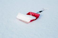 Rote Schaufel für die Schneeräumung, die im Schnee liegt Stockfoto