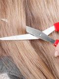 Rote Scheren auf blondem Haar Abschluss oben Lizenzfreie Stockfotografie