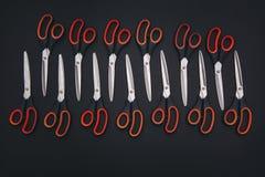 Rote Scheren sind auf der schwarzen Tabelle Stockfotografie