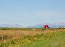 Rote Scheune auf dem Grasland Lizenzfreies Stockbild