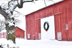 Rote Scheune im Winter mit einem Weihnachtskranz stockfotografie