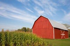 Rote Scheune mit Mais und drastischem Himmel Stockfotografie