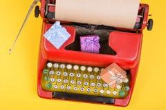 rote Schreibmaschine mit leerem Kraftpapier, Geschenkboxen auf gelbem Hintergrund stockfoto