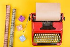 rote Schreibmaschine mit leerem Kraftpapier, Geschenkboxen auf gelbem Hintergrund lizenzfreies stockfoto