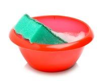 Rote Schüssel und grüner Schwamm mit Schaum Stockfotos