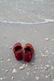 Rote Schuhe auf dem Strand Stockbild