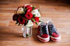 Rote Schuhe auf einem braunen Boden mit Blumenstrauß von Rosen Lizenzfreies Stockfoto