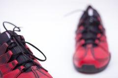 Rote Schuhe auf einem weißen Hintergrund stockbild