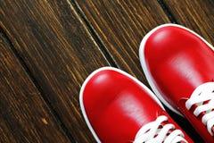 Rote Schuhe auf hölzernem Hintergrund Stockbilder