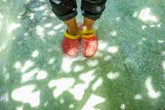 Rote Schuhe der touristischen Abnutzung stachen auf dem klaren Wasser im Nationalpark des erawan Wasserfalls lizenzfreie stockbilder