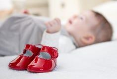 Rote Schuhe und Baby des Babys, die auf dem Hintergrund liegt Stockbilder