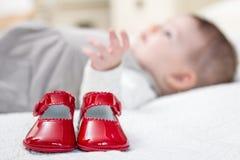 Rote Schuhe und Baby des Babys, die auf dem Hintergrund liegt Stockbild