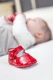 Rote Schuhe und Baby des Babys, die auf dem Hintergrund spielt Stockbilder