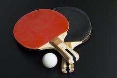 Rote, schwarze Schläger des Tischtennis und weißer Ball Stockfotografie