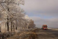 Rote schwere Fahrzeuge auf der Winterstraße Stockfotografie
