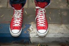 Rote Segeltuchturnschuhe auf Bürgersteig Stockfoto