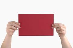Rote Seite in den Händen lizenzfreie stockfotos