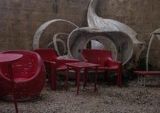Rote Stühle und Tabelle des äußeren leeren Cafés mit weißem modernem Entwurf, auf kleinen Steinen bedeckten Veranda lizenzfreies stockbild