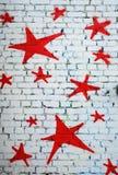 Rote Sterne auf weißer Backsteinmauer Stockfotos