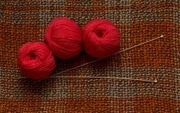 Rote Stränge, hölzerne Stricknadeln auf einer braunen Maschenware Stockbild