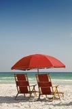 Rote Strand-Stühle und Regenschirm Stockfotografie