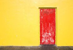Rote Tür auf gelber Wand Lizenzfreie Stockfotografie