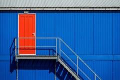 Rote Tür in einer blauen Fassade Lizenzfreies Stockfoto