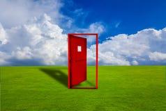 Rote Tür gesetzt auf einen Rasen im Freien mit Boden des blauen Himmels Stockfotos